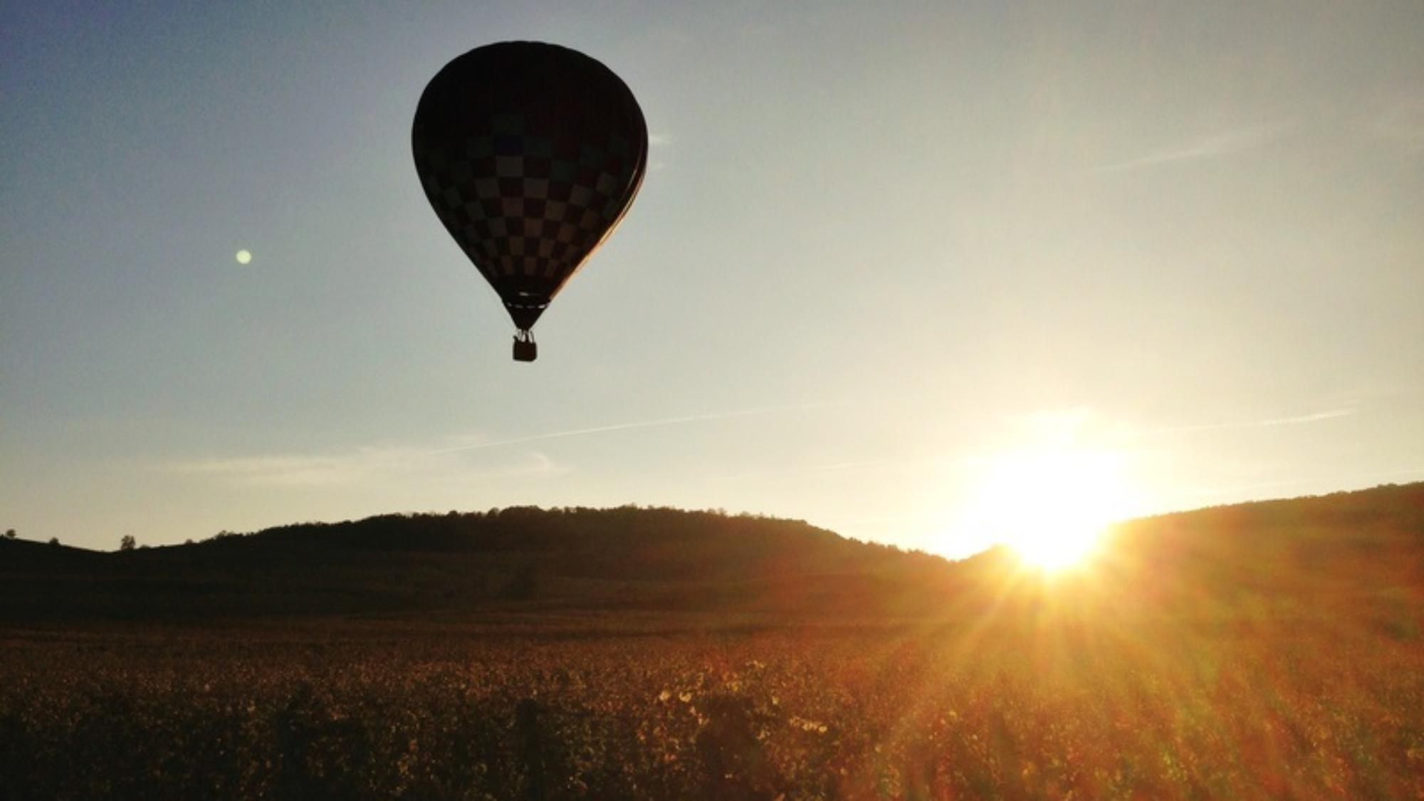 silhouette de montgolfire au soleil couchant